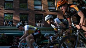 साइकिल सवारों को देखते लोग