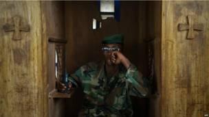 Un combattant rebelle du M23 assis dans un confessionnal à Rumangabo. Samedi 20 juillet. Photo AFP