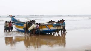 Un grupo de hombres levanta un bote en Andhra Pradesh, India