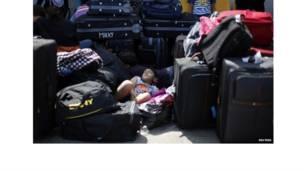 सूटकेसों के बीच सोता  लड़का