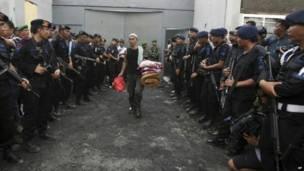 कैदी को सामन ले जाते देखती  पुलिस