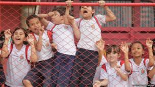 ब्राजील की राजधानी ब्राजीलिया में कुछ स्कूली बच्चे अभ्यास करती हुई ब्राजील की राष्ट्रीय टीम को देख कर उत्साह में चिल्लाते हुए.