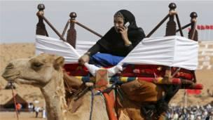 Une femme sur son chameau téléphonant avec un portable à la fantasia au Moussem à Tan Tan, dans le sud marocain. 07092013 Photo AP