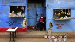 Une marchande attendant les clients devant sa boutique, à Kibera dans la banlieue de Nairobi.