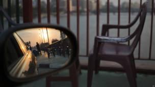 Un vendeur, dont la silhouete est réfléchie sur le rétroviseur d'une voiture, sur le pont du 6 Octobre au Caire. 28 09 2013 Photo AP