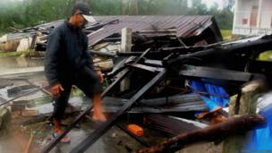 A man clearing debris after the typhoon. Photo by STR/AFP/Getty Images