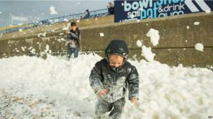 चक्रवात के ब्रिटेन के पहले तेज़ हवाएं चलने लगीं . तेज़ हवाओं के पहले समुद्र के फेन से ब्राइटन में खेलता यह बच्चा.