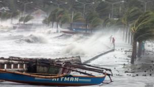 مواطنون (يمينا) يقفون إلى جوار البحر فيما تهب الرياح القوية