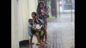 أم مع ابنائها فيما يضرب الإعصار هايان مدينة سيبو