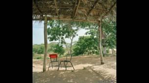 Sillas de estudiantes en una escuela elemental que tiene tres aulas, no calles de acceso, ni electricidad ni agua.