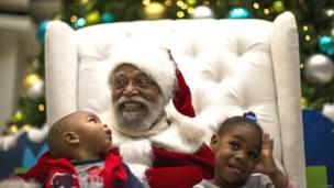 अमरीका,लॉस एंजिल्स, ब्लैक सैंटा, काला सांता, शापिंग मॉल, क्रिसमस, काले सांता पर विवाद, सांता के रंग को लेकर हंगामा, बच्चों के साथ सांता,