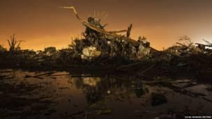 गत २७ मेमा अमेरीकाको ओक्लोहोमा शहरमा टोर्नाडो भनिने आँधीपछि भग्नावशेषको थुप्रोमाथि रहेको एक कार