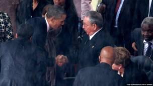 मण्डेलाको निधन भएपछि आयोजित स्मृतिसभामा  क्युबाका राष्ट्रपति राउल कास्ट्रोसंग हात मिलाउंदै अमेरिकी राष्ट्रपति बाराक ओबामा