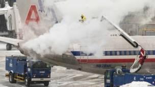 В Бостонском аэропорту рабочие заняты антиоблединительной обработкой самолетов