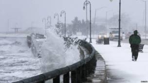 Мужчина на берегу под ударами волн