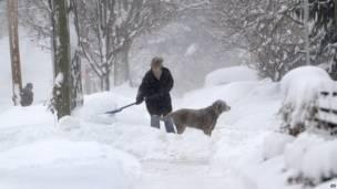 Мишель Коттке расчищает снег в компании своей собаки