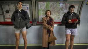 Un pasajero vestido en medio de dos participantes en el metro de Madrid.