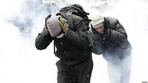 Протестующие закрывают уши, перебегая через задымленное пространство