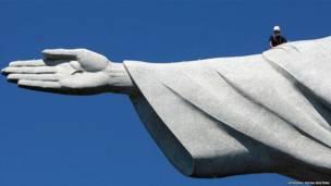 एक कारीगर रियो डी जेनरो में 'क्राइस्ट द रिडीमर' की मूर्ती के ऊपर हुए नुकसान का जायज़ा लेते हुए.  एक पहाड़ की चोटी पर बनी इस लाजवाब मूर्ती का एक अंगूठा बिजली गिरने की वजह क्षतिग्रस्त हो गया था.