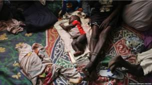 दक्षिण सूडान के मलकल के एक चर्च में एक नन्हा बच्चा ज़मीन पर अपनी माँ के बगल में सोते हुए. दक्षिण सूडान की सेना ने हाल ही में इस शहर को एक बड़ी लड़ाई के बाद कब्ज़े में लिया है.