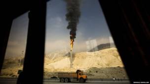 ईरान के दक्षिणी फ़ारस के में एक गैस उत्पादन इकाई से निकलती हुई एक लपट. ईरान और क़तर के बीच फ़ारस की खाड़ी में गैस के बेहद बड़े भंडार हैं जिनके भीतर 14 खरब क्यूबिक मीटर गैस होने के अनुमान हैं.