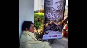 Hombre dormido frente a póster