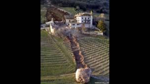 रॉन्ची दी टेमेनो के एक फॉर्म हाउस के पास भूस्खलन के कारण ऊँची पहाड़ी से नीचे आ गया एक विशाल शिलाखंड