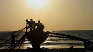 गोवा का समुद्रतट और जाल फैलाते मछुआरे
