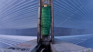 Explorador en saco de dormir en la parte alta de un puente