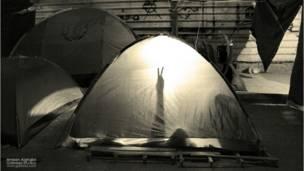 معتصم يرفع علامة النصر من داخل خيمة في ميدان التغيير بصنعاء - أمين الغابري 2011