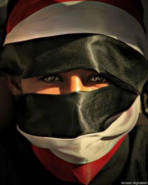 صورة لمتظاهر يغطي وجهه بعلم اليمن - أمين الغابري 2011