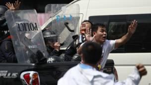 Seorang demonstran meminta rekannya menghentikan serangan. Foto: Wason Wanichakorn/AP