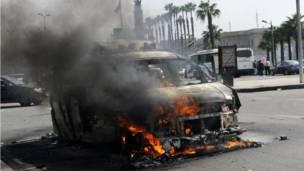 سيارة تحترق أمام جامعة القاهرة بعد أن اشعلها الطلاب