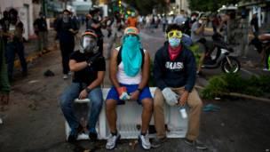 Manifestantes enmascarados descansan (Foto AP/Rodrigo Abd)