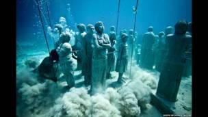 الفنان جيسون تايلور وفريقه يضعون التماثيل في قاع البحر.