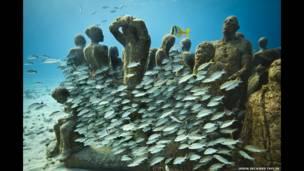 تمثال التطور الصمت، على عمق ثمانية أمتار، في متحف الفنون تحت الماء بمدينة كانكون الساحلية وجزيرة موخيريس في المكسيك للفنان جيسون ديكاريس تايلور