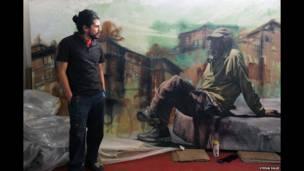 तस्वीर में दीवारों पर कलाकारी करने वाले अल्फ्रेडो गुटिएरेज़ अपनी एक प्रोर्ट्रेट के साथ दिखाई दे रहे हैं. चित्र दीवार पर बने चित्र में एक अमरीकी बेघर आदमी बाजा कैलिफोर्निया (मैक्सिको) के तिजुआना इलाके में है.