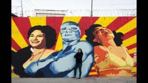 अना मारिया क्रुज उर्फ अना फॉर्मिस्मो किउदाद जुआरेज में एक दीवार पर बनाए गए अपने एक चित्र के साथ.
