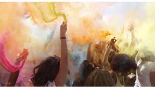 المحتفلون يرشون مساحيق الألوان في الهواء