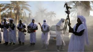 مجموعة من الرجال يرتدون ملابس بيضاء ويحملون آلات موسيقية