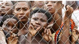 مجموعة من النساء خلف سياج حديدي