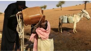 امرأة تساعد طفلة على شرب المياه