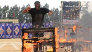 رجل أمن يقفز فوق حاجز مشتعل