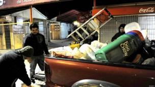 एक गाड़ी पर सामान लादते लोग