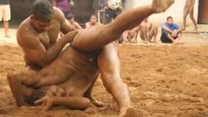 अखाड़े में कुश्ती लड़ते दो पहलवान