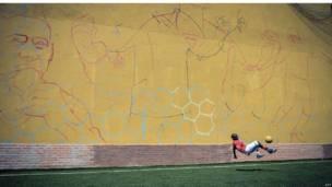 طفل يلعب الكرة وخلفه جدار كبير