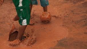 İnsanlar bir su birikintisinde futbol oynuyor