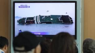 Люди смотрят по телевизору новости о затонувшем пароме