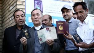مجموعة من الرجال يحملون جوازات سفرهم العراقية
