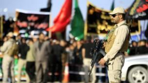 جندي يقف أمام تجمع انتخابي حاملا السلاح